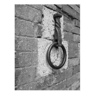 Ancient iron hoop hanging on stone wall postcard