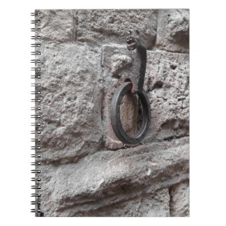 Ancient iron hoop hanging on stone wall spiral notebook