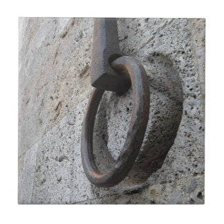 Ancient iron hoop hanging on stone wall tile