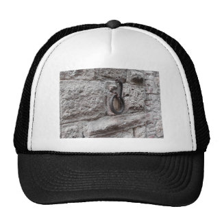 Ancient iron hoop hanging on stone wall trucker hat