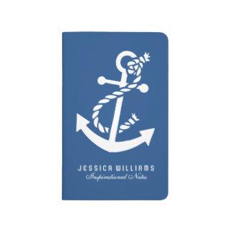 Ancla náutica blanca del barco sobre azules cuadernos grapados