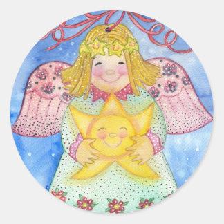 Ángel del navidad con el pegatina de la estrella