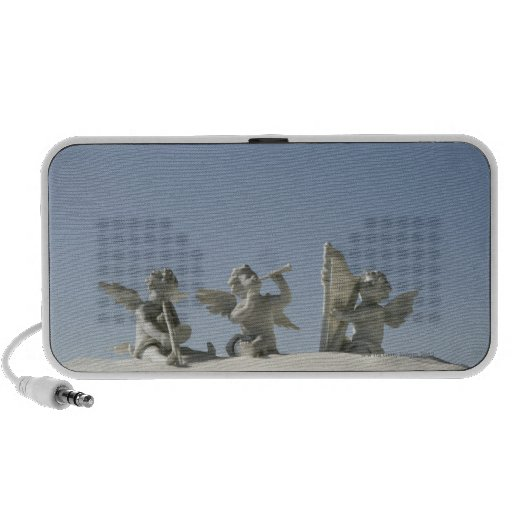 Angel figurines with musical instruments on portable speaker