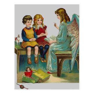 Ángel que enseña a dos niños lindos postal