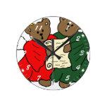 Ángeles del oso de peluche en trajes rojos y verde reloj