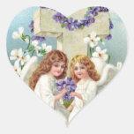Ángeles lindos con la cruz y las flores pegatina en forma de corazón