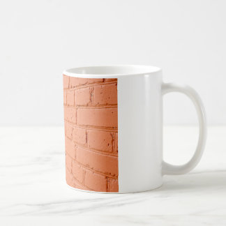 Angle view of a brick wall with a layer of red pai coffee mug