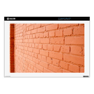 Angle view of a brick wall with a layer of red pai laptop skin