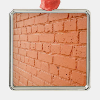 Angle view of a brick wall with a layer of red pai metal ornament