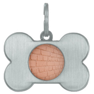 Angle view of a brick wall with a layer of red pai pet ID tag