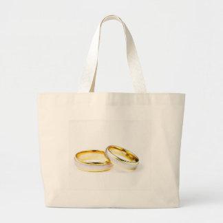 Anillos de bodas de oro en el fondo blanco bolsa tela grande