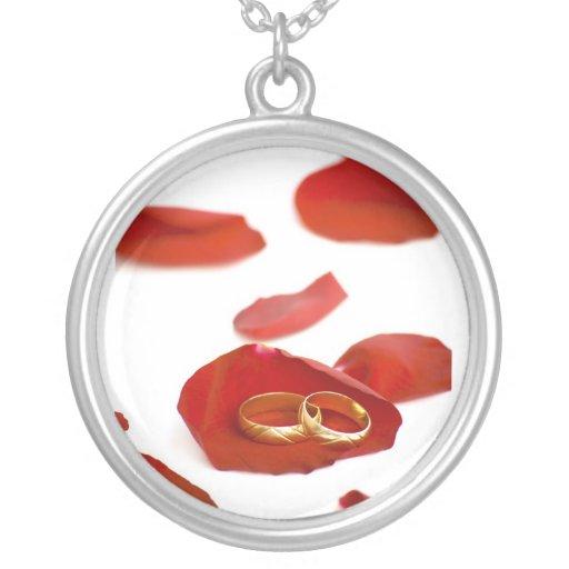 anillos de bodas sobre los pétalos color de rosa colgante redondo