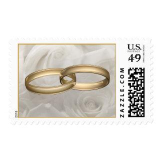 Anillos de bodas y rosas blancos franqueo