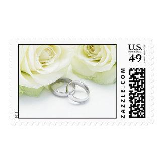 Anillos de bodas y rosas franqueo
