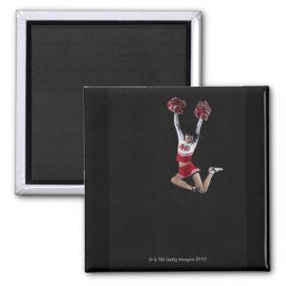 Animadora femenina joven que salta en el aire, bra imán cuadrado