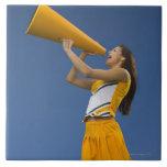 Animadora femenina que grita en el megáfono azulejo cuadrado grande