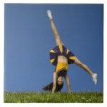 Animadora femenina que hace el cartwheel azulejo cuadrado grande