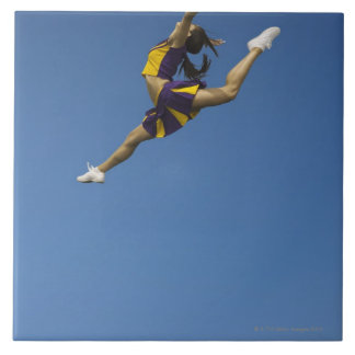 Animadora femenina que salta arriba para arriba en azulejo cuadrado grande