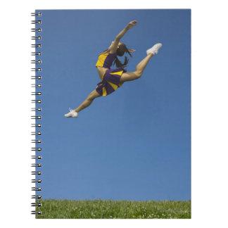 Animadora femenina que salta arriba para arriba en spiral notebook