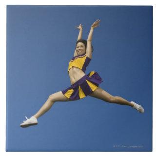 Animadora femenina que salta en aire azulejo cuadrado grande