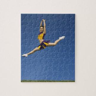 Animadora femenina que salta en aire rompecabezas con fotos