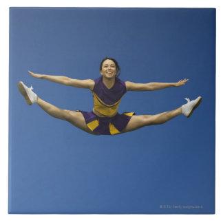 Animadora femenina que salta en el aire 3 azulejo cuadrado grande
