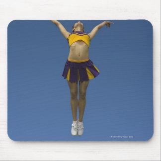 Animadora femenina que salta en el aire, vista del tapete de raton