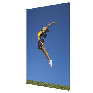 Animadora femenina que salta en el aire vista lat impresiones en lona