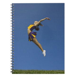 Animadora femenina que salta en el aire, vista libreta espiral
