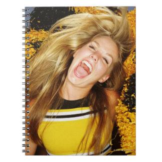 Animadora que mueve de un tirón el pelo, riendo, note book