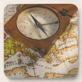 Antique compass on map beverage coaster