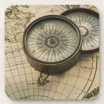 Antique compass on map drink coaster