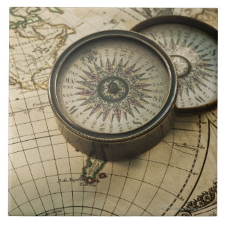 Antique compass on map tile