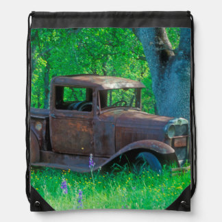 Antique rusted truck in a meadow drawstring backpack