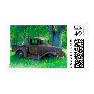 Antique rusted truck in a meadow postage