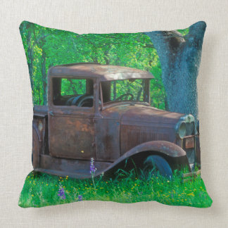Antique rusted truck in a meadow throw pillow