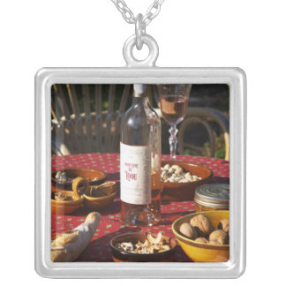 Aperitif and appetizers prepared: bread, olives, square pendant necklace
