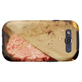 Aplanando una hamburguesa Patty con una espátula e Galaxy S3 Fundas