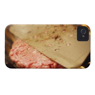 Aplanando una hamburguesa Patty con una espátula iPhone 4 Coberturas