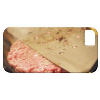 Aplanando una hamburguesa Patty con una espátula iPhone 5 Funda