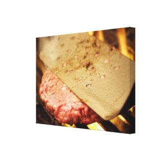Aplanando una hamburguesa Patty con una espátula Impresiones En Lienzo Estiradas