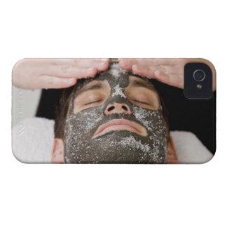 Aplicación de la mascarilla del skincare con la funda para iPhone 4