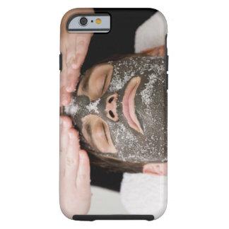 Aplicación de la mascarilla del skincare con la funda resistente iPhone 6