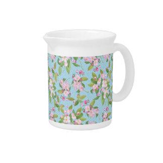 Apple rosado florece floral en fondo azul frondoso jarra de beber