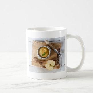 Applesauce with cinnamon in stoneware bowl coffee mug
