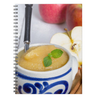 Applesauce with cinnamon in stoneware bowl spiral note book