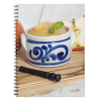 Applesauce with cinnamon in stoneware bowl spiral note books