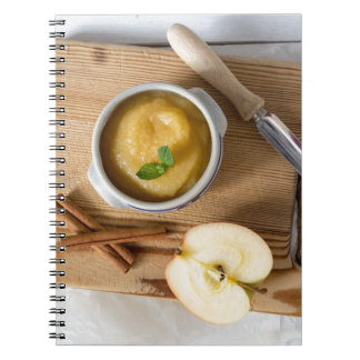Applesauce with cinnamon in stoneware bowl spiral notebooks