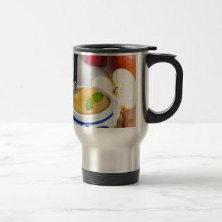 Applesauce with cinnamon in stoneware bowl travel mug
