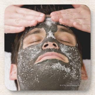 Applying skincare face mask with salt coaster